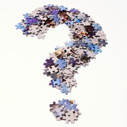 A big question mark made by stacking various jigsaw puzzle pieces and then making them take that specific shape. The pieces are scrambled and on both sides against a white background.